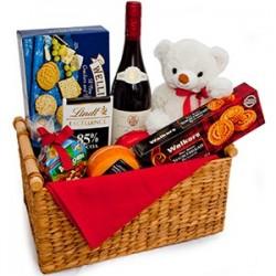 Cesto regalo con orsetto di peluche bottiglia vino e cioccolato
