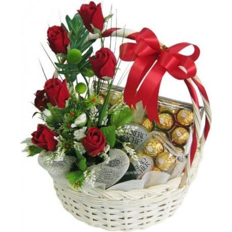 Cesto di fiori bellissimi di rose rosse e composizione con cioccolatini