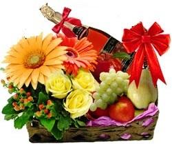 Cesto con fiori freschi colorati frutta mista e spumante