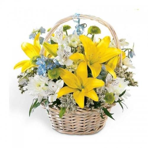 Cesto di fiori freschi composizione con lilium gialli e fiori blu