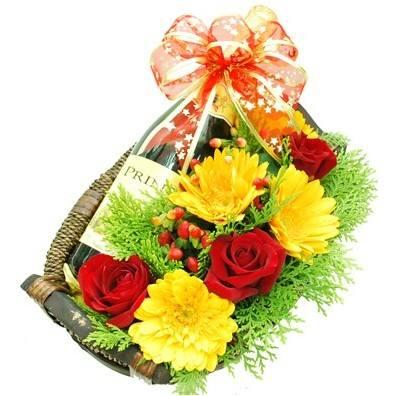 Cesto di fiori freschi gialli e rossi composizione con bottiglia vino