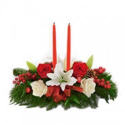Composizione di Natale con 2 candele e fiori misti sul rosso e bianco