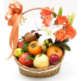 Cesto di fiori freschi bianchi e arancio composizione con frutta fresca
