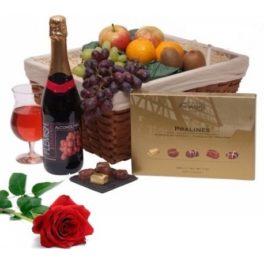 cesto gastronomico da regalo con frutta vino rosso e una rosa rossa